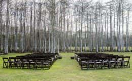 Rustic wedding ceremony under the cypress trees
