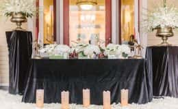 Dramatic sweetheart table with gold urns and florals