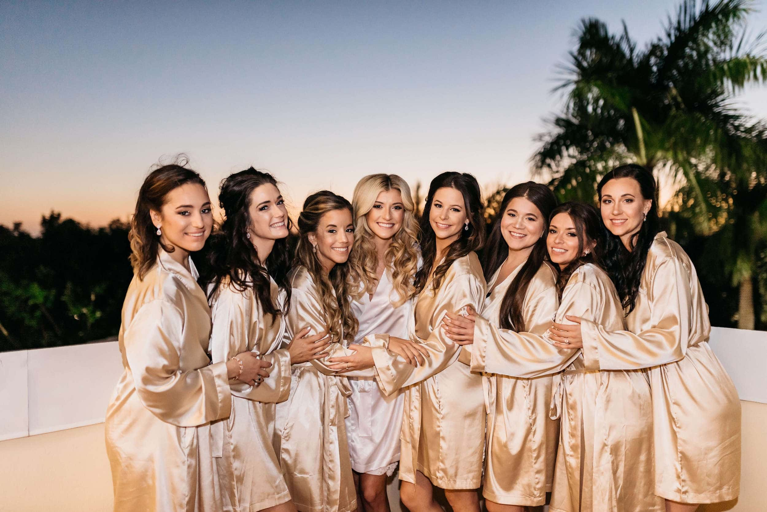 Blushing bride and her beautiful bridesmaids in robes