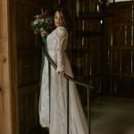 bride stands on spiral staircase with bouquet