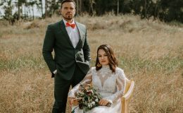 Boho chic bride and groom in vintage chair lace wedding dress and hunter green suit