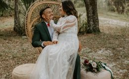Bride caresses groom's face in peacock chair