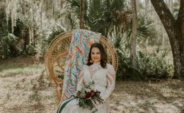 Bride in lace wedding dress sits in a peacock chair under moss covered oak tree