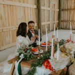 married couple cheers at sweetheart table at barn