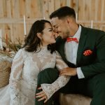 bride and groom share a look as they sit at their wood sweetheart table in barn reception