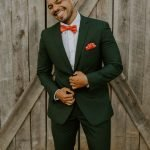 groom in hunter green suit is all smiles before barn wedding