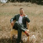 groom in a hunter green suit relaxing in a vintage boho chair in a field