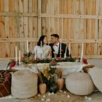 couple sits at sweetheart table and look at each other