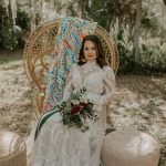 Bright colored fabric drapes a peacock chair with boho bride