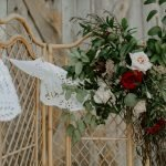 florals and greenery on bamboo wedding arch at barn