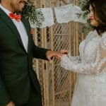 groom has ring put on his finger by his bride during barn wedding
