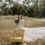 In a field stands a boho bride in lace wedding dress and floral bouquet