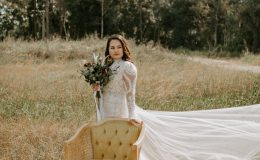 boho bride in lace wedding dress and floral bouquet stands in a field