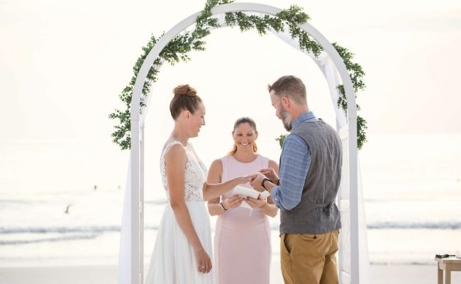 Groom putting wedding ring on bride